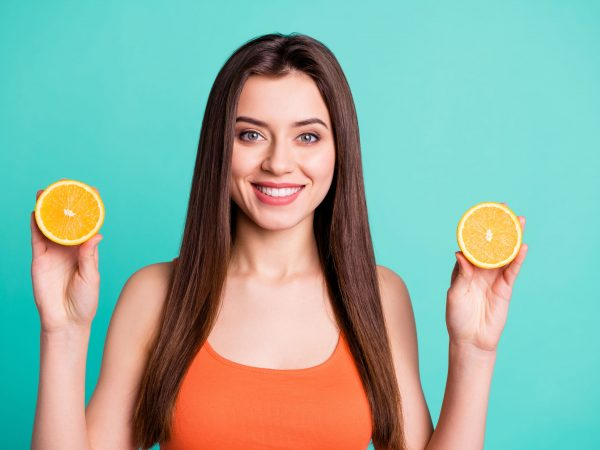 Close up photo beautiful amazing her she lady hold arms two citrus useful slices products advertising nutrition freshness wear casual orange tank-top isolated bright teal turquoise background.