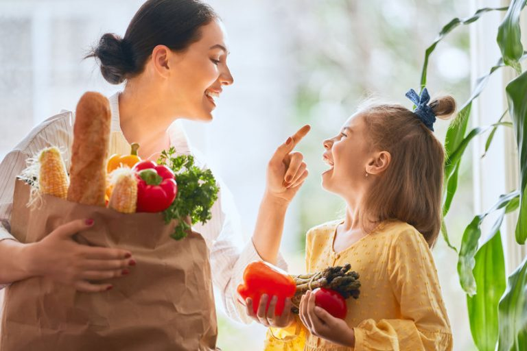 Woman and child laughing with fresh food