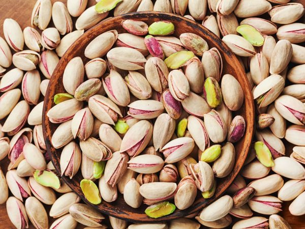Bowl of pistachio nuts on wooden table top view. Healthy food and snack.